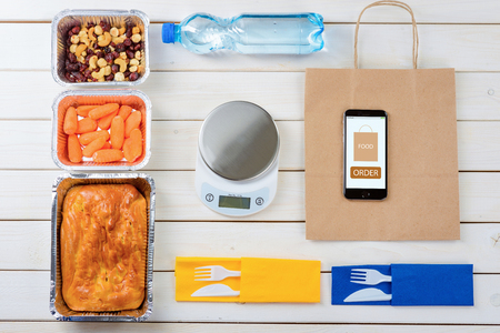 Bottle of water, a kitchen scale, a pie, baby carrots, nuts and dried fruit, a paper bag, a smartphone with Food Order sign and plastic cutlery on wooden surface. Healthy food delivery. Stock Photo
