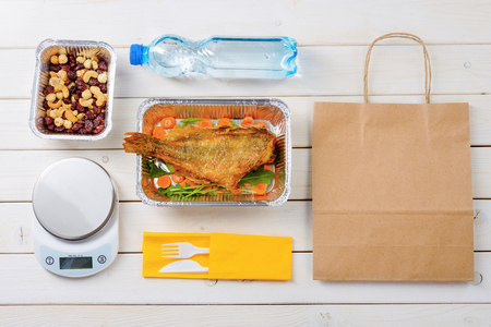 Kitchen scale, hazelnuts and dates, fish with arugula and sliced carrot, plastic cutlery, a bottle of water and a paper bag on the wooden background. Top-view image. Ordering diet food. Stock Photo