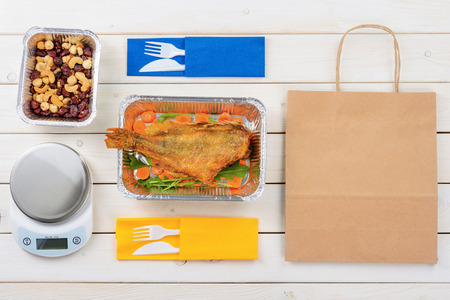 Paper bag, fish with arugula and sliced carrot, nuts and dried fruit, a food scale, plastic forks and knives on the wooden surface, a top-view image. Healthy takeout for two.