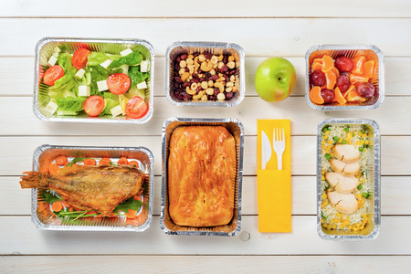 Fish, a pie, rice with corn and lean chicken, plums and tangerines, an apple, tomato and feta salad, hazelnuts, dried fruit and plastic cutlery on the wooden surface. Nutritional meal delivery. Stock fotó