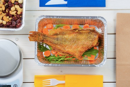 Appetizing fish with vegetables, cashews, hazelnuts and dried fruit, a kitchen scale and plastic flatware on the light wooden surface, close-up. Healthy takeout food.