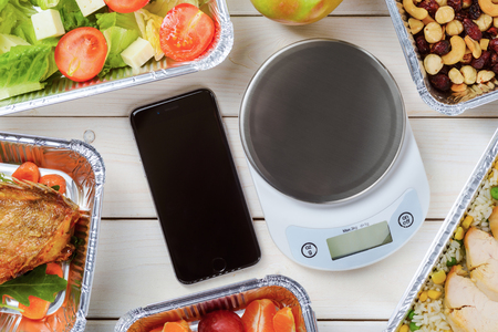Kitchen scale, a smartphone on the wooden surface, close-up. Tomato and lettuce salad, cashews, hazelnuts and dried fruit, lean chicken and fish. Healthy delivery.