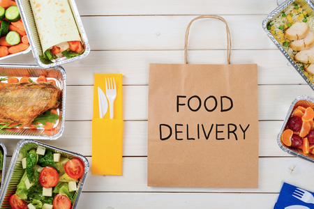 Fish, a vegetable roll, tomato and lettuce salad, plastic flatware and a paper bag with Food Delivery sign, close-up. Rice with chicken, fruit, wooden surface. Dinner for busy people. Stockfoto