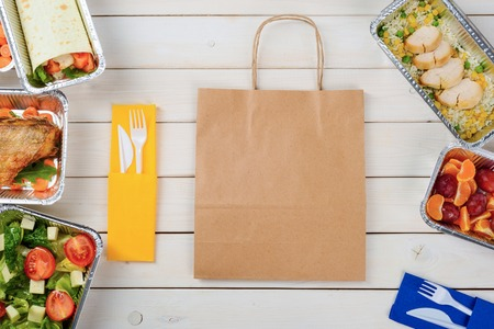 Vegetable roll, fish, tomato and lettuce salad, plastic flatware and a paper bag, a top-view image. Rice with chicken, plums and tangerines on the wooden surface. Ordering food.