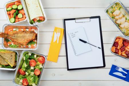 Nota carta e una penna sulla superficie in legno. Forchetta e coltello di plastica, pesce con rucola, carotine, panino, insalata di pomodori e feta, pollo, mandarini e prugne. Contare le calorie. Archivio Fotografico