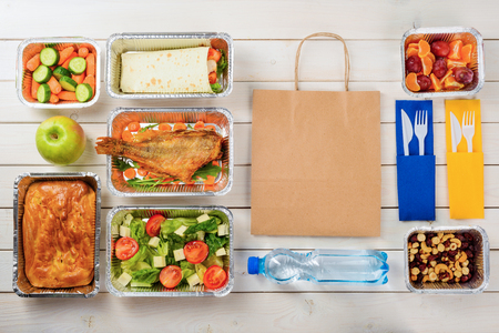 Plastic cutlery, a paper bag, a bottle of water, fish, feta and lettuce salad, a pie, an apple, a vegetable roll, baby carrots, plums, tangerines, nuts and dates on the wooden surface. Order food.