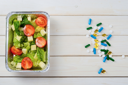 Tomato, feta and lettuce salad and supplements on the wooden surface, close-up, a top-view image. Real food versus pills. Stockfoto