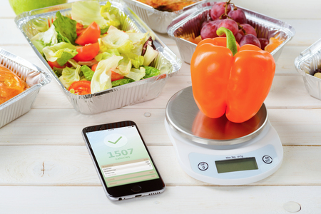 Kalorienzähler-App auf dem Smartphone, eine Küchenwaage und ein frischer Pfeffer auf der Holzoberfläche, Nahaufnahme. Salat und Tomatensalat, Trauben auf dem Hintergrund. Kalorien zählen.
