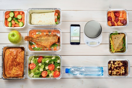 Calorie counter app and a kitchen scale on the wooden surface. Plums, cheese sandwiches, nuts, a bottle of water, tomato and lettuce salad, vegetables, a pie and fish. Slim down. Stockfoto