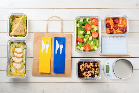 Writing-book and a pencil, a kitchen scale, a paper bag and plastic flatware, rice and chicken, cheese and lettuce sandwiches, nuts and dates, tomato salad and fruit. Food journal practice. Stock Photo