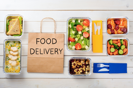 Paper bag with Food Delivery sign. Cashews, hazelnuts and dates, carrots and cucumbers, rice with chicken, sandwiches, tomato salad, plastic cutlery and fruit, wooden surface. Ordering your meal. 免版税图像