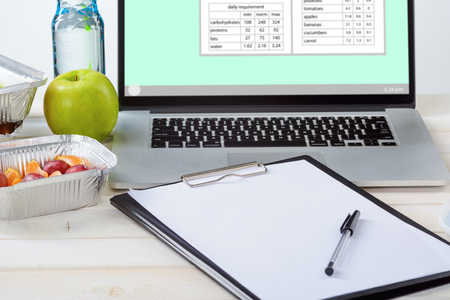 Laptop with nutrient calculations, note paper and a pen, a bottle of water, an apple, plums and tangerines, a white table, close-up. Dietitian career. Archivio Fotografico - 107007197