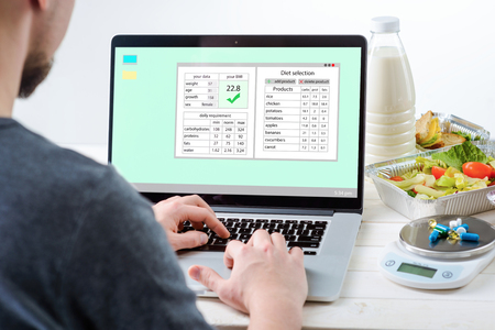 Man at the laptop with a nutrition plan on the screen, close-up. Bottle of milk, salad, sandwiches, a food scale and pills, white background. Registered nutritionist. 版權商用圖片