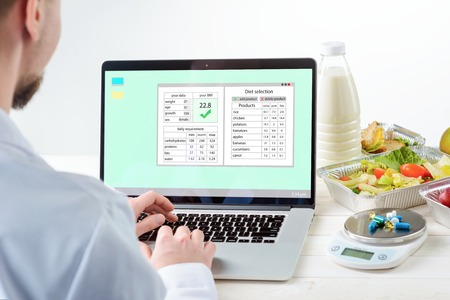 Young man at the laptop with a nutrition plan on the screen, close-up. Tomato salad, a bottle of milk, sandwiches, a food scale and pills, white background. Registered dietitian.