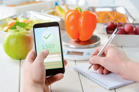 Calorie counter app on the smartphone, making notes, close-up. Grapes, an apple on the wooden surface, a pepper on the food scale on the background. Weight loss journey. Standard-Bild