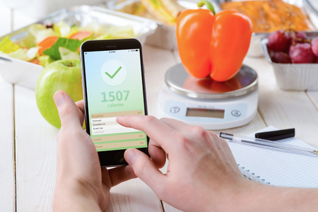 Smartphone with a calorie counter app, close-up. Paper notebook, a food scale, a pepper, an apple, salad, grapes and a pie on the background. Dieting,