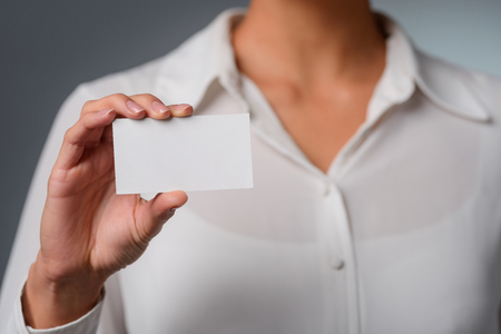 Woman holds a visit card.
