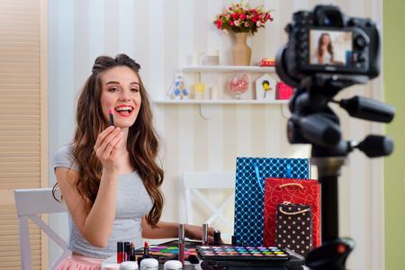 Attractive woman presenting lipstick Stock Photo - 108965618