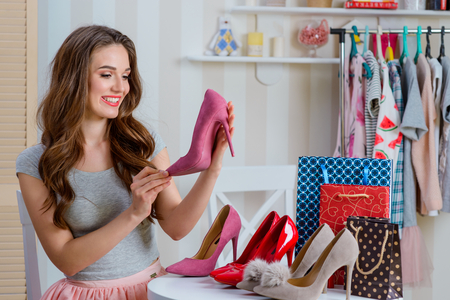 Cute girl holds pink shoe