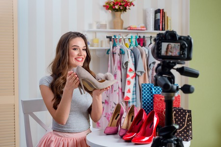 Smiling girl holds gray shoes
