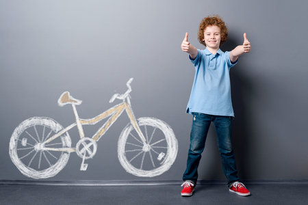Satisfied boy and yellow bicycle Фото со стока