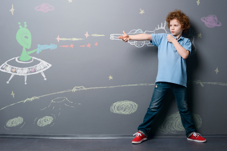 Boy fights with alien soldier Stock Photo