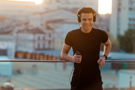 Joyful man running and listening