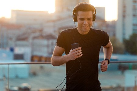 Handsome man running and listening Stock Photo