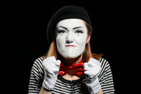Angry female mime on black
