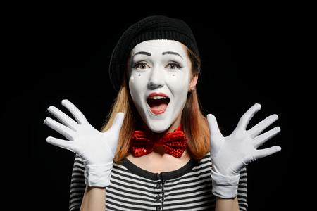 Happy female mime on black