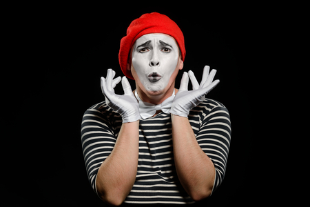 Worried male mime on black