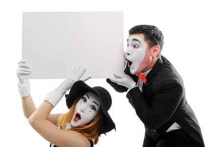 Surprised mimes holding blank placard