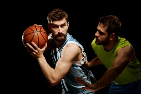 Two sportmen playing basketball