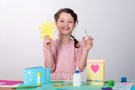 Young girl holding cutouts shapes
