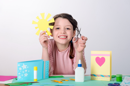Happy child doing a collage Stock Photo