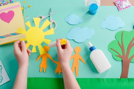 Girl Applying glue on paper shape