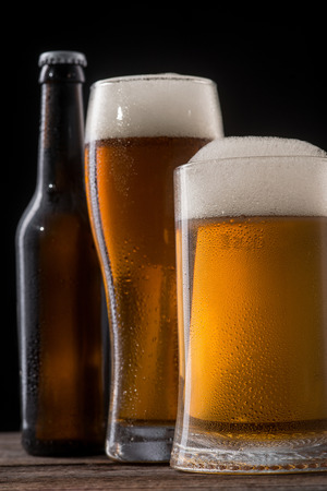 Light beer with large head. A bottle made of dark glass, a tall beerglass and a pint full of malted drink. Vertical still life. Stock Photo