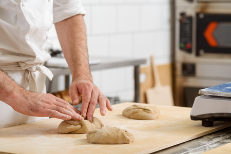 Baker is kneading dough Stockfoto