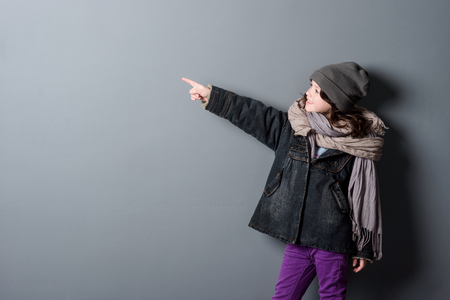 Girl pointing on grey background