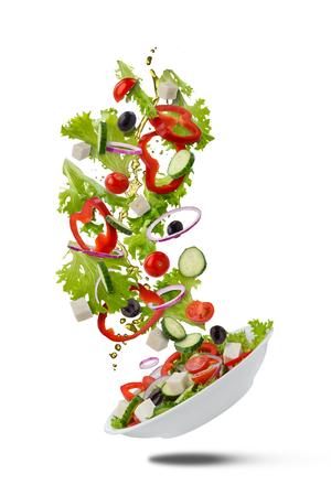 Flying Greek salad on white