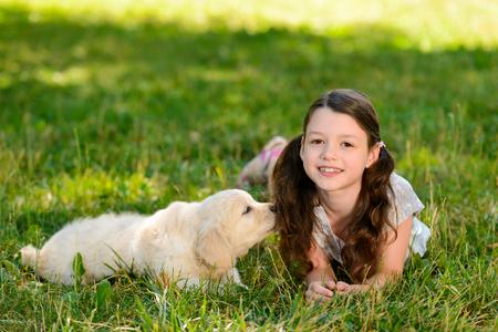 Girl and dog laying on grass