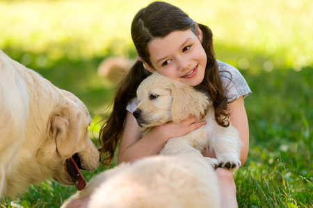 Girl holding golden retriever cub
