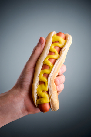 Male hand holding hot dog