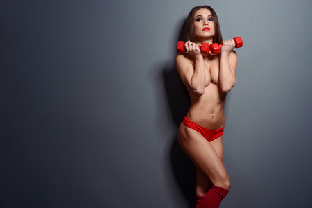 Fit sportswoman posing with dumbbells