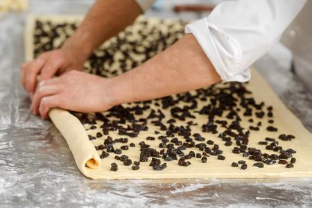 Baker is making dough roll