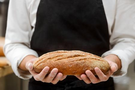 Baker holding a fresh bread