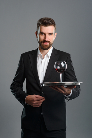 Sommelier holding tray with wineglass