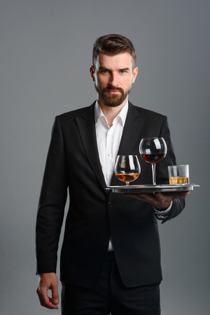 Waiter carrying tray with drinks