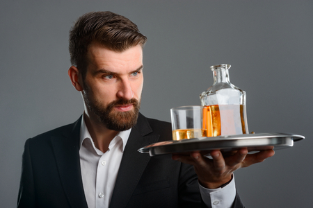 Waiter carrying tray with whisky