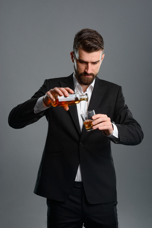 Concentrated man pouring whisky Banco de Imagens